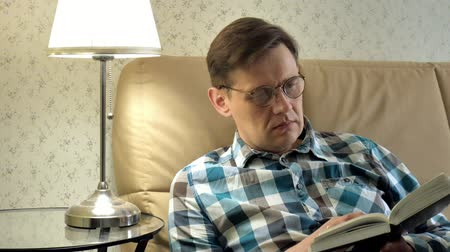 homely : Mature man lying on bed reading a book at home in bedroom