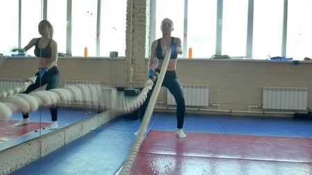 cordas : Athletic Female Working Out Using Battle Ropes. High-intensity interval training.