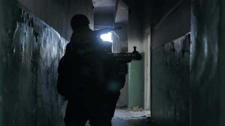 combate : Soldiers in camouflage with combat weapons sneak along the corridors of the old building, the military concept