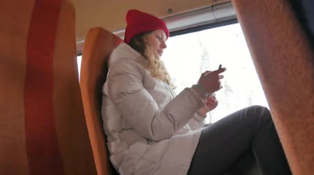 deep autumn : young cheerful woman in a red hat, traveling by bus on a sad day. She takes pictures on a smartphone