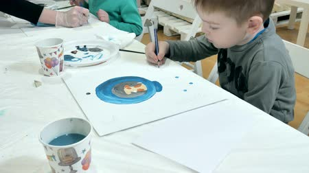 преподаватель : Children boys sitting together around the table in classroom and drawing. With them is their young and beautiful teacher.