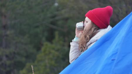 kaynatmak : Attractive young woman tourist in a red hat sits in a tourist tent and drinks tea from a thermos Stok Video