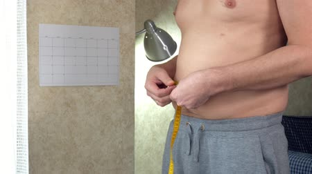 упитанность : A fat man measures his waist, a big beer belly, a healthy lifestyle