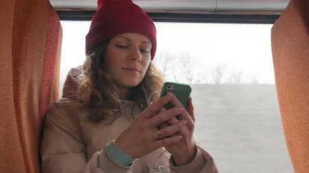 deep autumn : young cheerful woman in a red hat, traveling by bus on a sad day. She listening to music