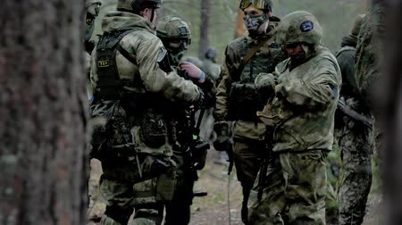 paintball : Soldiers in camouflage prepare for battle and check out equipment and weapons Stock Footage