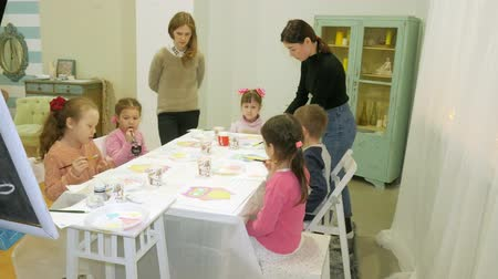 učit : Children boys and girls sitting together around the table in classroom and drawing. With them is their young and beautiful teacher.
