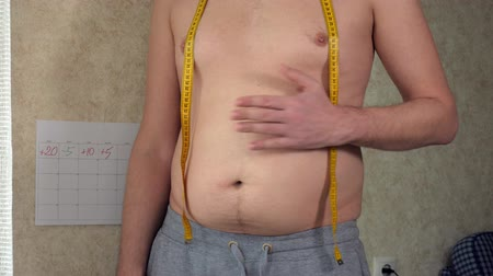 bel ölçüsü : A fat man measures his waist, a big beer belly, a healthy lifestyle picks up fat folds