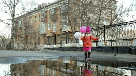 pocsolya : Little beautiful girl jumping on puddles after rain Stock mozgókép