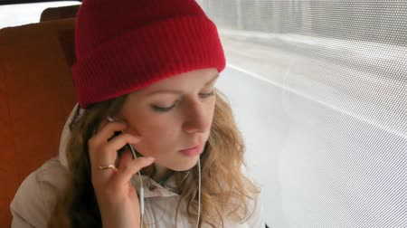 deep autumn : young cheerful woman traveling by bus on a sad day. She looks out the window