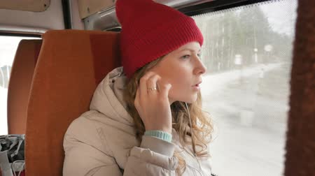 dull : young cheerful woman traveling by bus on a sad day. She looks out the window
