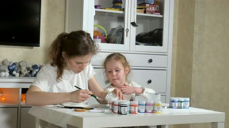 рисунки : Mother and child paint with colored fingers. Games with children affect the development of early children. Стоковые видеозаписи