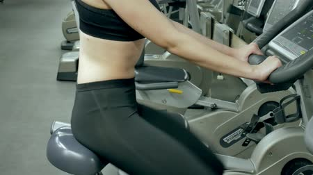 tornaterem : Young attractive woman enhancing her endurance while working out on an exercycle. portrait of a beautiful girl in the gym on a stationary bike. young woman on exercise bike aerobic exercise Stock mozgókép