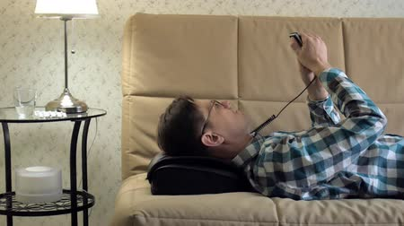 masszírozó : man lies on the couch at home, under the head of a massager, relaxed state