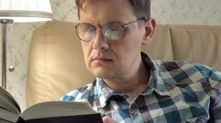 утешитель : Mature man lying on bed reading a book at home in bedroom