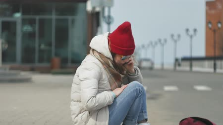на камеру : Young beautiful woman in a red hat wearing sporty warm clothes and rollers, sitting on the asphalt road and talking on the phone Стоковые видеозаписи
