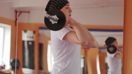 divoký : Woman kickboxer is training in a sports studio with barbell