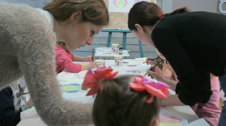 kryty : Children boys and girls sitting together around the table in classroom and drawing. With them is their young and beautiful teacher.