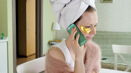 mascarar : attractive business woman applying cosmetic facial spots at home, talking on the phone Stock Footage