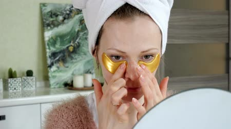 анти : attractive woman spplying cosmetic facial patches at home