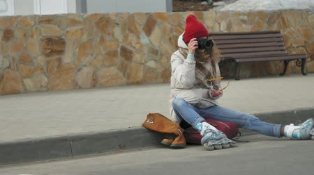 paten yapma : Young beautiful woman in red hat wearing sporty warm clothes and rollers, sitting on the asphalt road and taking pictures on a vintage camera
