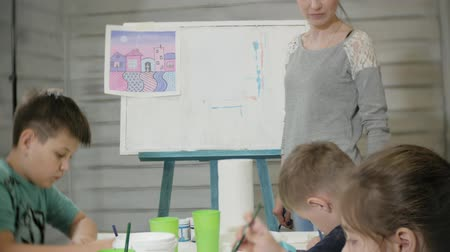 учитель : Children boys and girls sitting together around the table in classroom and drawing. With them is their young and beautiful teacher.