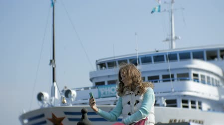 turk : Woman relaxing in the port with cruise ships in the background Stock Footage