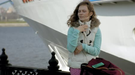személyszállító hajó : Woman relaxing in the port with cruise ships in the background Stock mozgókép