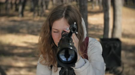 teleskop : Attractive woman looks through a telescope in a forest on the river bank