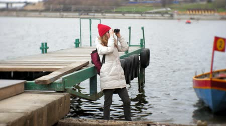 binocular : A beautiful woman in a jacket and a red hat is standing on the dock and looking through binocular