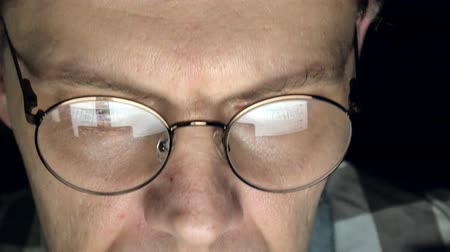 komisyoncu : A man in glasses works late at night. He looks worried, he sees on the computer screen in front of him, a close-up