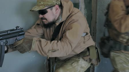 guerra : Soldiers in camouflage with military weapons knock out the door and do the seizure of the old building, the military concept Stock Footage