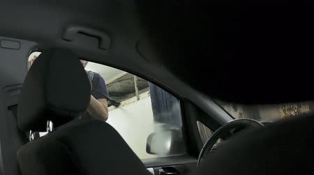 myjnia samochodowa : car passing through the car wash, a person washes the car with a non-contact sink, a view from inside the car