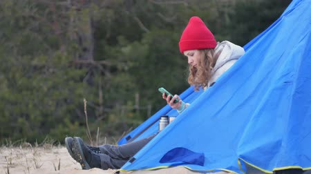 brew tea : Attractive young woman tourist in a red hat sits in a tourist tent and drinks tea from a thermos Stock Footage