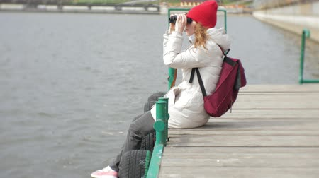 pier : A beautiful woman in a jacket and a red hat is standing on the dock and looking through binocular