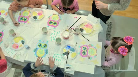 crayon : Children boys and girls sitting together around the table in classroom and drawing. Stock Footage