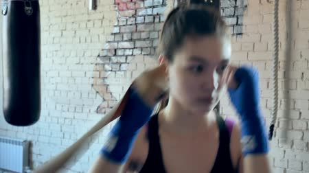 divoký : Beautiful kickboxing woman training punching with rubber band in fitness studio fierce strength fit body kickboxer series Dostupné videozáznamy