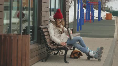 paten yapma : Young beautiful woman in a red hat wearing sporty warm clothes and rollers, sitting on a wooden bench drinking tea from a bottle