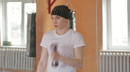 divoký : Woman kickboxer is training in a sports studio with dumbbells
