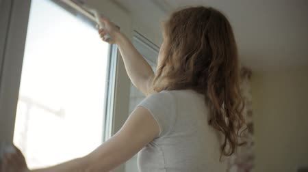 auxiliar : attractive girl washes windows at home. To clean up the house.
