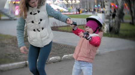 zasnoubený : Mom and daughter ride on roller skates. Girl learning to roller skate, and falls. Mom teaches daughter to ride on rollers Dostupné videozáznamy