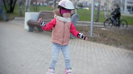 paten yapma : Mom and daughter ride on roller skates. Girl learning to roller skate, and falls. Mom teaches daughter to ride on rollers Stok Video