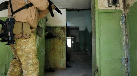 kurşun : Soldiers in camouflage with combat weapons sneak along the corridors of the old building, the military concept