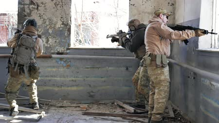 винтовка : Soldiers in camouflage with a military weapon aiming through the rifle sight through the window of an old building, the military concept Стоковые видеозаписи