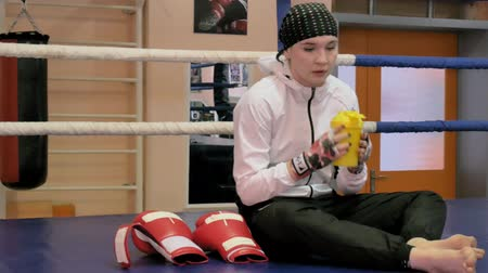 ivászat : Woman kickboxer sits in the ring and drinks water after training