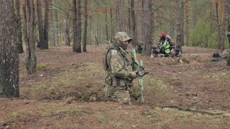 combate : Soldiers in camouflage with combat weapons are being fired in the shelter of the forest, the military concept