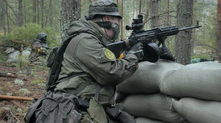 conflito : Soldiers in camouflage with combat weapons are being fired in the shelter of the forest, the military concept