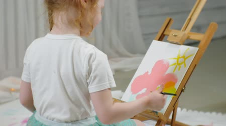 crayon : Beautiful red-haired girl sits on the floor in the studio in front of the easel and draws a brush and colored paints Stock Footage
