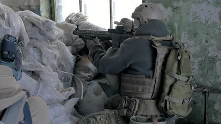 arma de fogo : Soldiers in camouflage with combat weapons are being fired in the shelter of the old building, the military concept