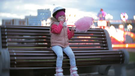 bank : Beautiful little girl sitting on a bench in an amusement park, eating pink sweet cotton candy rolling on roller skates