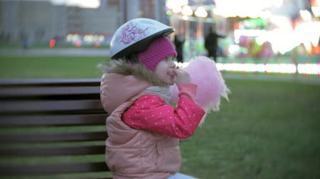 algodão : Beautiful little girl sitting on a bench in an amusement park, eating pink sweet cotton candy rolling on roller skates